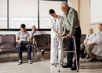 Senior men being helped by female nurse to walk the Zimmer frame with people sitting in hospital lobby